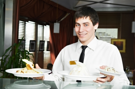 trays: waiter in uniform at restaurant Stock Photo