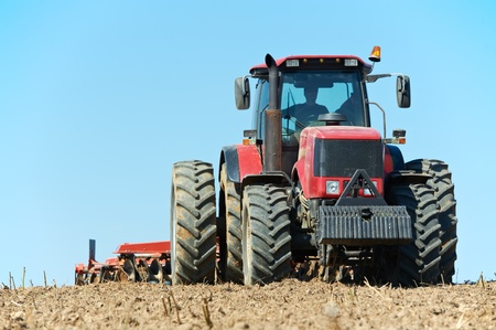 plough machine: Ploughing tractor at field cultivation work