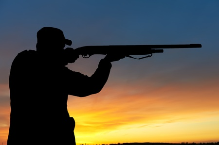 hombre disparando: Hunter con cañón de fusil Foto de archivo