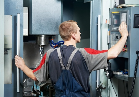 cnc: worker at machining tool workshop Stock Photo