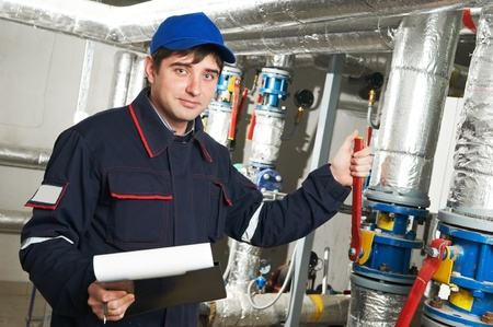 labourer: heating engineer repairman in boiler room Stock Photo