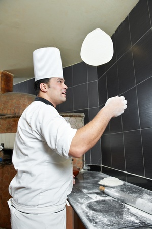 Pizza baker juggling with dough photo