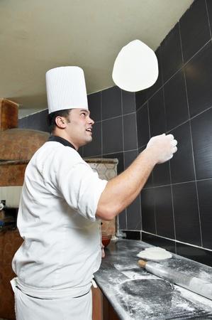 preparing dough: Pizza baker juggling with dough Stock Photo