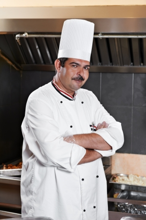 chef in uniform at kitchen photo