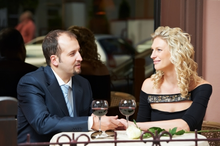 Man and girl with wine at cafe on a date photo