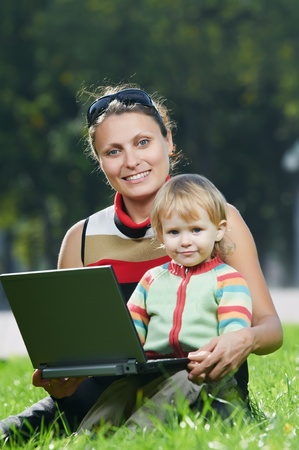 Smiling pregnant woman with laptop photo