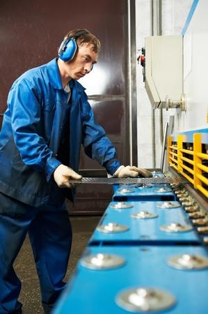 굽힘: 작업자 운영 단두대 가위 기계 스톡 사진