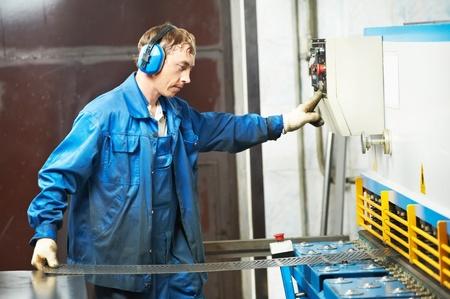 guillotine: worker operating guillotine shears machine