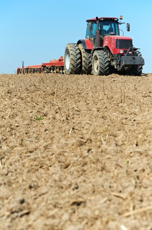 Ploughing tractor at field cultivation work photo