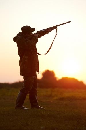 hombre disparando: cazador apuntando con una pistola rifle