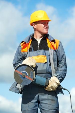 hard worker: ritratto di operaio edile con la smerigliatrice Archivio Fotografico
