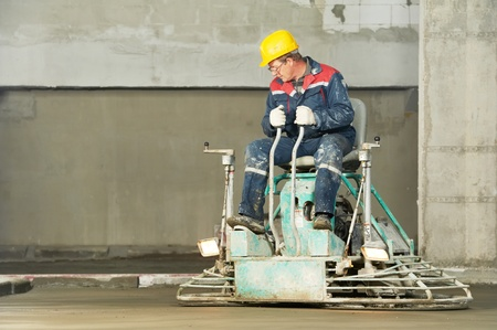 grinding: Worker trowelling and finishing of concrete Stock Photo
