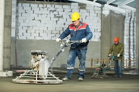 polishing: Worker trowelling and finishing of concrete Stock Photo