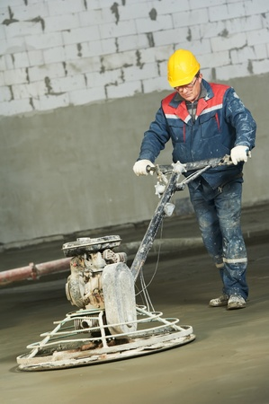 floor covering: Worker trowelling and finishing of concrete Stock Photo