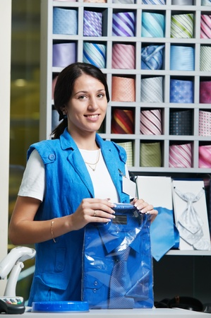 shop assistant: Young salesperson girl at clothes shop