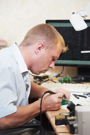 operative: worker soldering microchip scheme