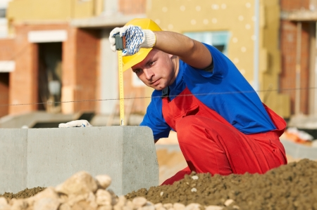 inspecting: builder with measure tape Stock Photo