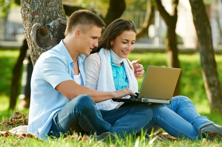 netbook: Two smiling young students outdoors Stock Photo