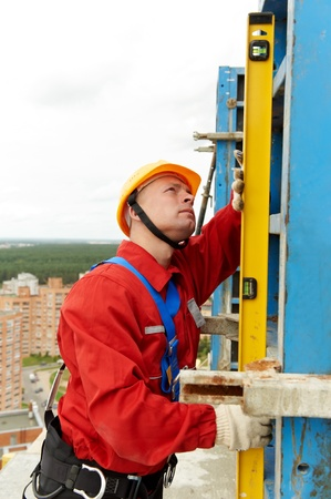 inspecting: builder with level Stock Photo