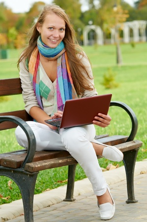 One smiling young girl with laptop outdoors photo