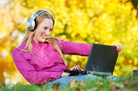 laptop outside: Woman with headphones and laptop autumn outdoors