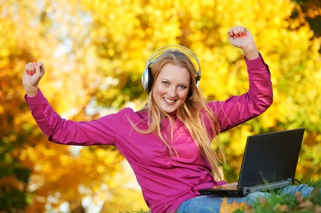 Woman with headphones and laptop autumn outdoors photo