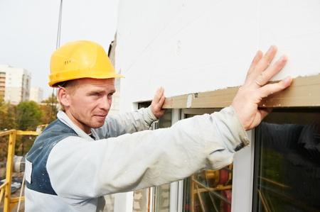 house inspection: builder facade plasterer worker Stock Photo