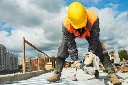 constructor: constructor de trabajo con la amoladora de corte Foto de archivo