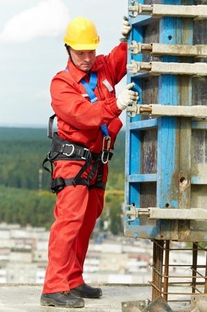 operarios trabajando: montador de los trabajadores en el sitio de la construcción