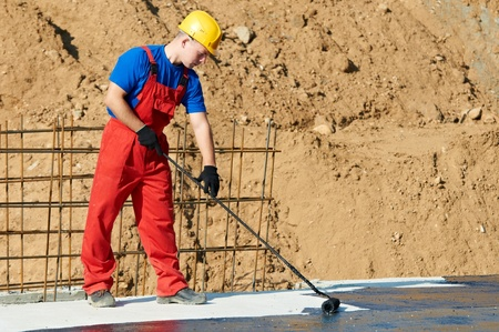 roofing membrane: builder worker at roof insulation work