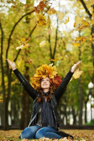 Woman with maple wreath at autumn outdoors photo