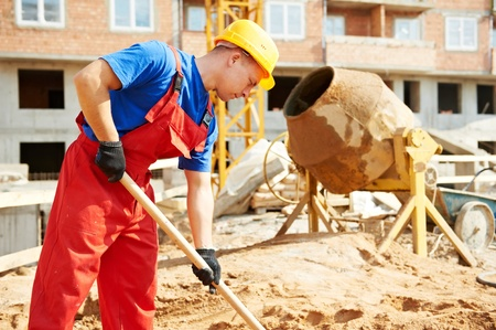 cement solution: builder worker at construction site with shovel Stock Photo