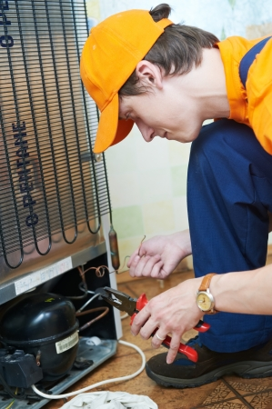 repairmen: repair work on fridge appliance