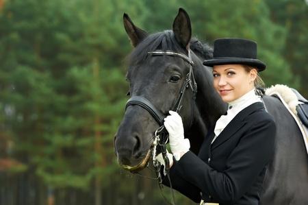 horsewoman jockey in uniform with horse photo