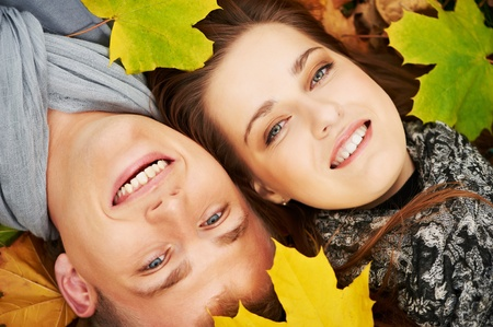 lying on leaves: Young couple at autumn outdoors