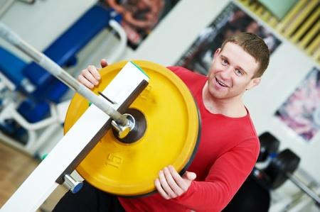 bodybuilder loading weight at sport gym photo
