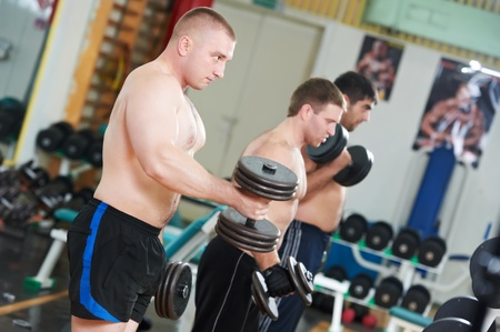 bodybuilders lifting weight at sport gym photo