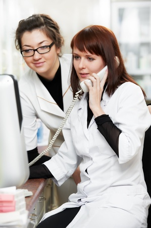 medical services: Pharmacy chemist women in drugstore with phone Stock Photo