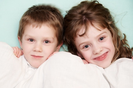 bedspread: close-up portrait of two children in bed Stock Photo