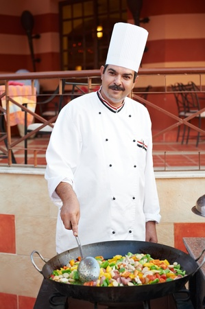 Arab chef frying meat on pan photo
