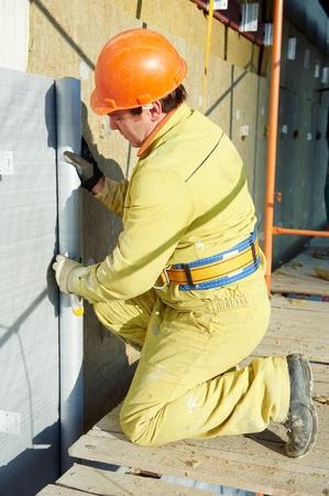 building external: Facade Plasterer at exterior insulation work Stock Photo