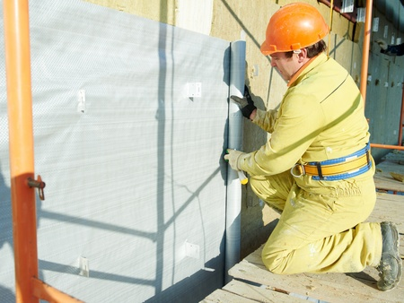plastering: Facade Plasterer at exterior insulation work Stock Photo