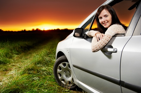 Smiling woman in the car at sunset Stock Photo - 11304783