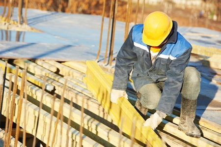 cast in place: construction worker preparing formwork
