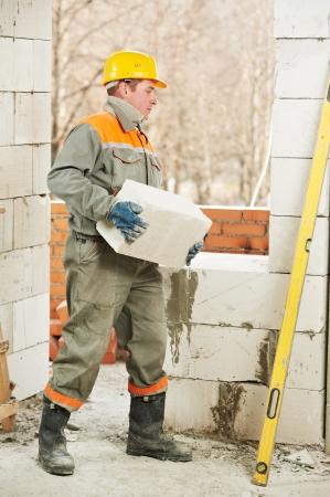 bricklayer at construction masonry works photo