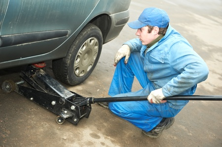 machanic repairman at tyre fitting with car jack photo