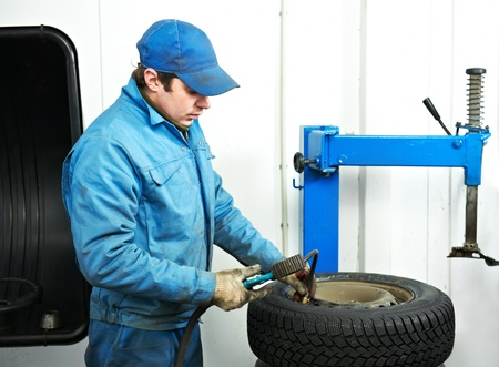 machanic repairman at tyre fitting photo