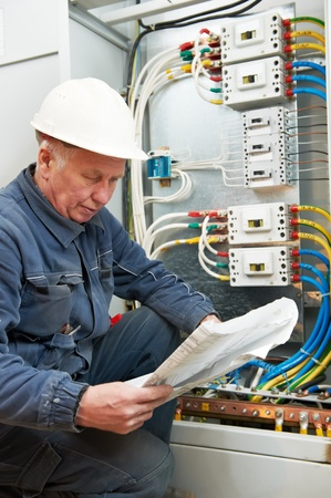 Electrician at wiring with working drawings photo