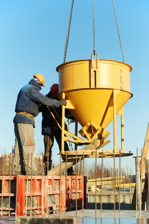 formwork: construction workers pouring concrete in form