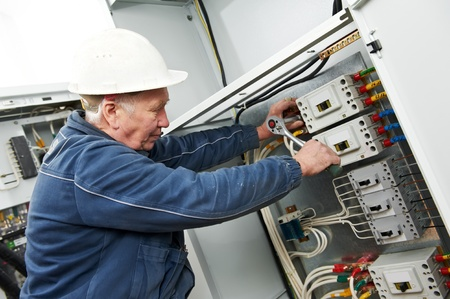 maintenance man: Electrician tighten the screws with spanner Stock Photo